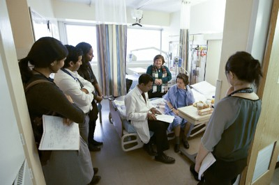 Dr. Sinha reviews patient chart with team